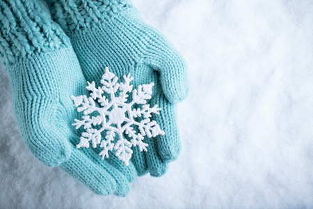 wonderful: Female hands in light teal knitted mittens with sparkling wonderful snowflake on a white snow background.