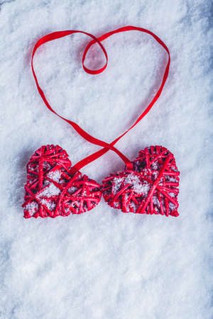 tied together: Two beautiful romantic vintage red hearts tied together with a ribbon on a white snow winter background