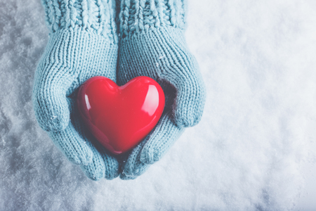 hands holding heart: Woman hands in light teal knitted mittens are holding a beautiful glossy red heart in a snow winter background. Stock Photo