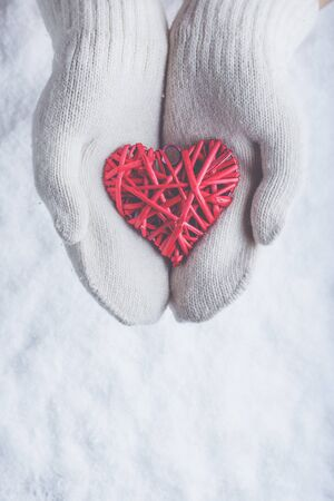 white heart: Female hands in white knitted mittens with a entwined vintage romantic red heart on a winter snow background.