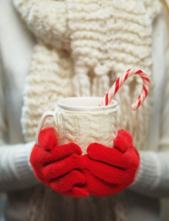 red gloves: Woman hands in woolen red gloves holding a cozy mug with hot cocoa, tea or coffee and a candy cane. Stock Photo