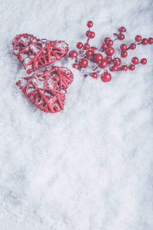 Two red hearts with mistletoe berries on a white snow winter background.