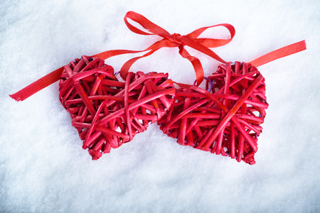 entwined: Two beautiful romantic vintage red hearts together on a white snow winter background.