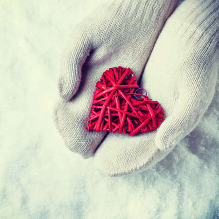 entwined: Female hands in white knitted mittens with a entwined vintage romantic red heart on a snow background.