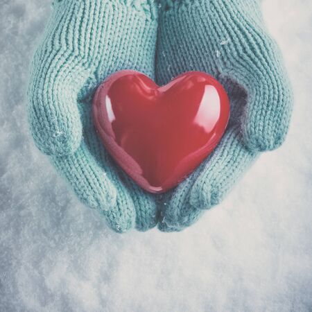 Female hands in light teal knitted mittens with a glossy red heart on snow