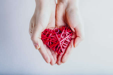 entwined: Female hands with a entwined vintage romantic red heart on a snow background.