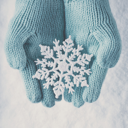 winter fashion: Female hands in light teal knitted mittens with sparkling wonderful snowflake on a white snow background.
