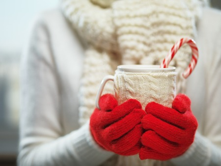 hot: Woman hands in woolen red gloves holding a cozy mug with hot cocoa, tea or coffee and a candy cane. Stock Photo