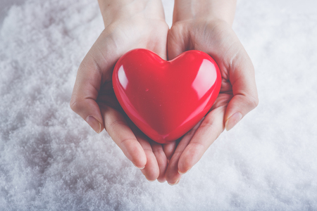 glossy: Woman hands are holding a beautiful glossy red heart in a snow winter background. Stock Photo