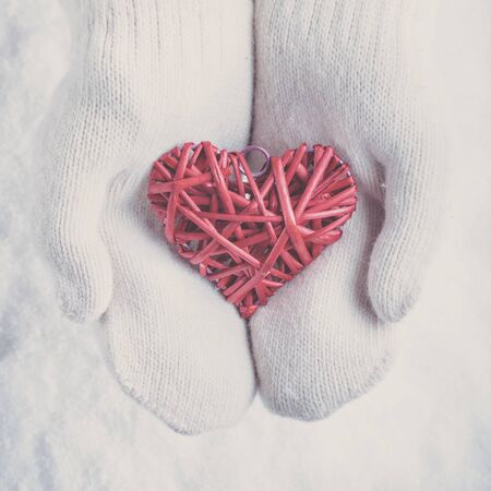 Woman hands in knitted mittens are holding a beautiful entwined vintage romantic red heart in a snow background. Stock Photo