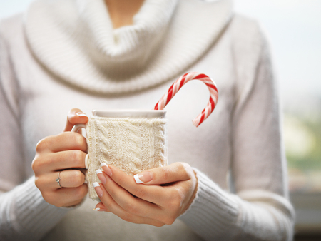 fall winter: Woman hands with elegant french manicure nails design holding a cozy knitted mug with cocoa, tea or coffee and a candy cane. Stock Photo