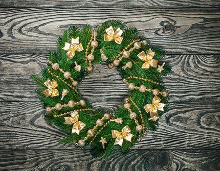 door leaf: Christmas wreath on a rustic wooden front door. Stock Photo