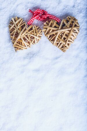 Two entwined beige flaxen hearts tied together with a ribbon on white snow.