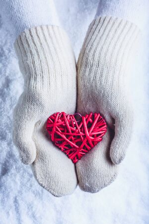 heart hands: Female hands in white knitted mittens with a entwined vintage romantic red heart on a winter snow background.
