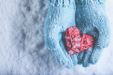 entwined: Woman hands in light teal knitted mittens are holding a beautiful a entwined vintage romantic red heart in a snow background.