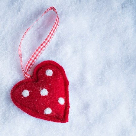 suave: Red toy suave heart on a frosty white snow winter background.