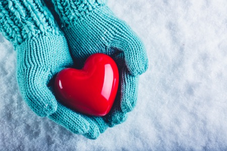 Woman hands in light teal knitted mittens are holding a beautiful glossy red heart in a snow winter background. Stock Photo