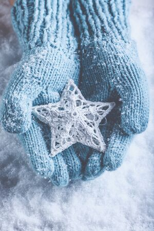 Female hands in light teal knitted mittens with entwined white star.