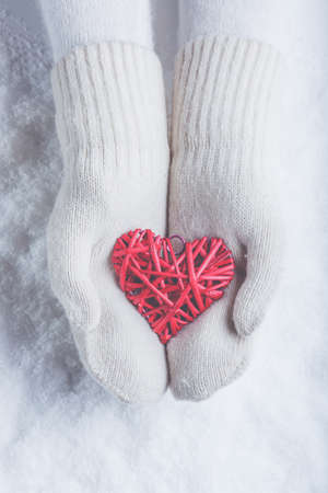 winter fashion: Female hands in white knitted mittens with a entwined vintage romantic red heart on a winter snow background.