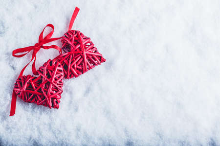 tied together: Two beautiful romantic vintage red hearts tied together with a ribbon on a white snow winter background. Love and St. Valentines Day concept. Stock Photo