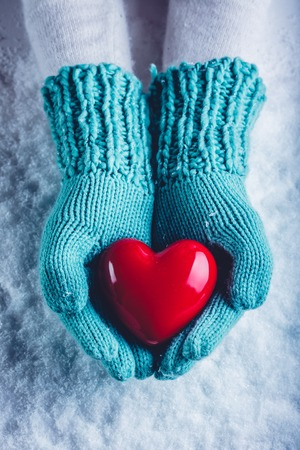 hands holding heart: Woman hands in light teal knitted mittens are holding a beautiful glossy red heart in a snow winter background. Love and St. Valentine cozy concept. Stock Photo