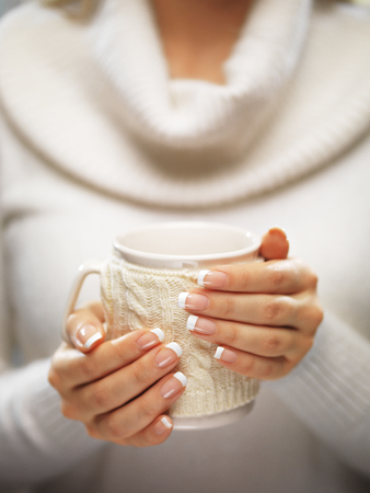 Woman hands with elegant french manicure nails design holding a cozy knitted mug. Standard-Bild