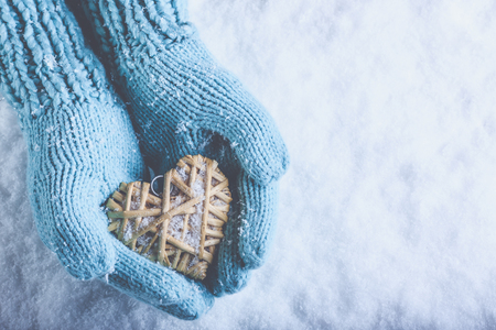 flaxen: Female hands in light teal knitted mittens with entwined beige flaxen heart on a white snow winter background.