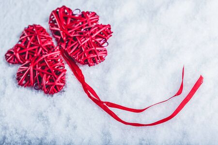red clover: beautiful romantic vintage red hearts together in clover shape on a white snow background. Stock Photo