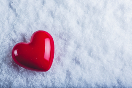 december: Red glossy heart on a frosty white snow winter background.