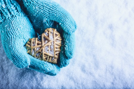 heart hands: Female hands in light teal knitted mittens with entwined beige flaxen heart on a white snow winter background