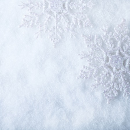 Two beautiful sparkling vintage snowflakes on a white frost snow background.