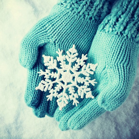 snowflake snow: Female hands in light teal knitted mittens with sparkling wonderful snowflake on a white snow background.