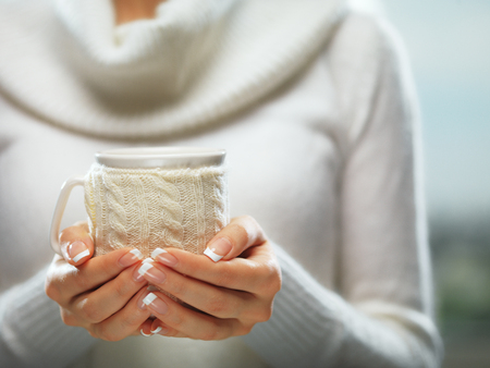 warm drink: Woman hands with elegant french manicure nails design holding a cozy knitted mug. Stock Photo