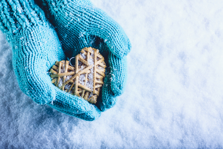 heart hands: Female hands in light teal knitted mittens with entwined beige flaxen heart on a white snow winter background.