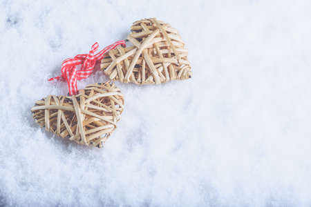 flaxen: Two beautiful romantic vintage entwined beige flaxen hearts tied together with a ribbon on a white snow winter background.