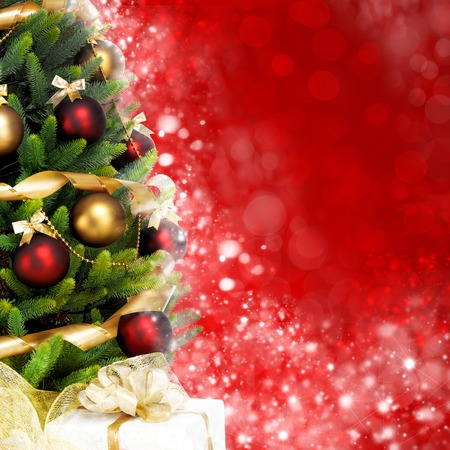 holiday backgrounds: Magically decorated Fir Tree with balls, ribbons and garlands on a blurred Christmas-red shiny and sparkling background.