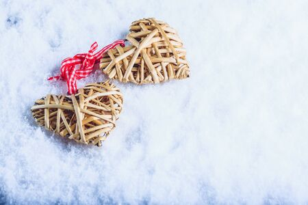 tied together: Two beautiful romantic vintage entwined beige flaxen hearts tied together with a ribbon on a white snow winter background.