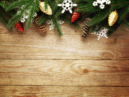 retro christmas: Christmas fir tree with decoration on wooden board background with copy space
