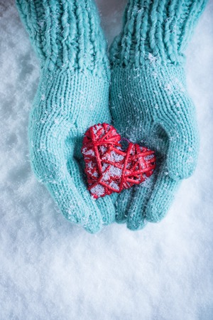 hands holding heart: Female hands in teal knitted mittens with a entwined vintage romantic heart on a snow background. Stock Photo