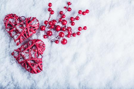 muerdago: Dos hermosos corazones rojos vendimia románticas con bayas de muérdago en un fondo blanco de nieve en invierno.