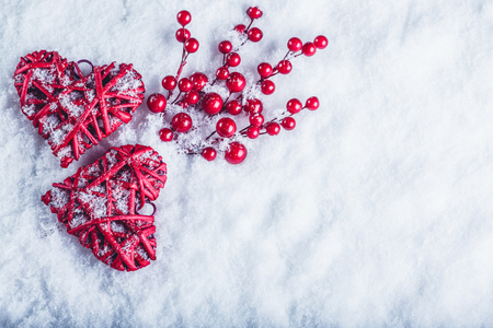 hearts: Two beautiful romantic vintage red hearts with mistletoe berries on a white snow winter background. Stock Photo