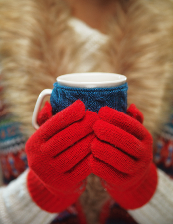 warmth: Woman hands holding a cozy knitted mug
