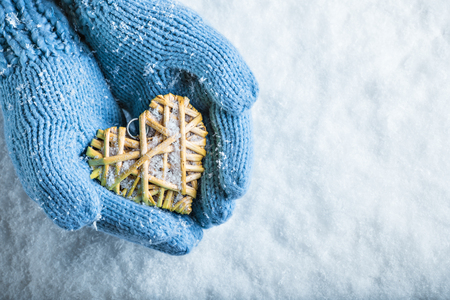 entwined: Female hands in teal knitted mittens with a entwined vintage romantic heart on a snow background. Stock Photo