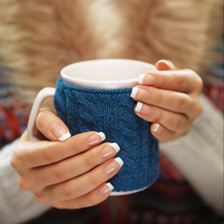 hot drink: hands with elegant french manicure nails design holding a cozy knitted mug.