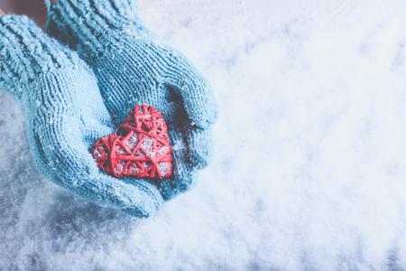 Vrouw handen in het licht blauwgroen gebreide wanten zijn met een mooie een verstrengeld vintage romantische rood hart op een achtergrond van sneeuw. Stockfoto