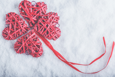 entwined: beautiful romantic vintage red hearts together in clover shape on a white snow background. Stock Photo