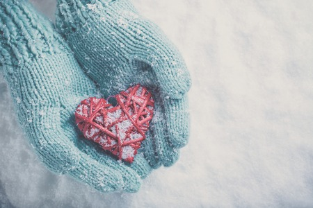 Woman hands in light teal knitted mittens are holding a beautiful glossy red heart in a snow winter background Archivio Fotografico