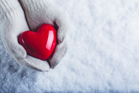 Female hands in white knitted mittens with a glossy red heart on a snow winter background. Standard-Bild