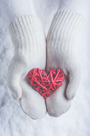 entwined: Female hands in white knitted mittens with a entwined vintage romantic red heart on a winter snow background