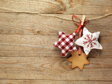 Gingerbread cookies and christmas decorations hanging over wooden background.